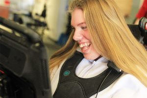 AAC user smiling using her device