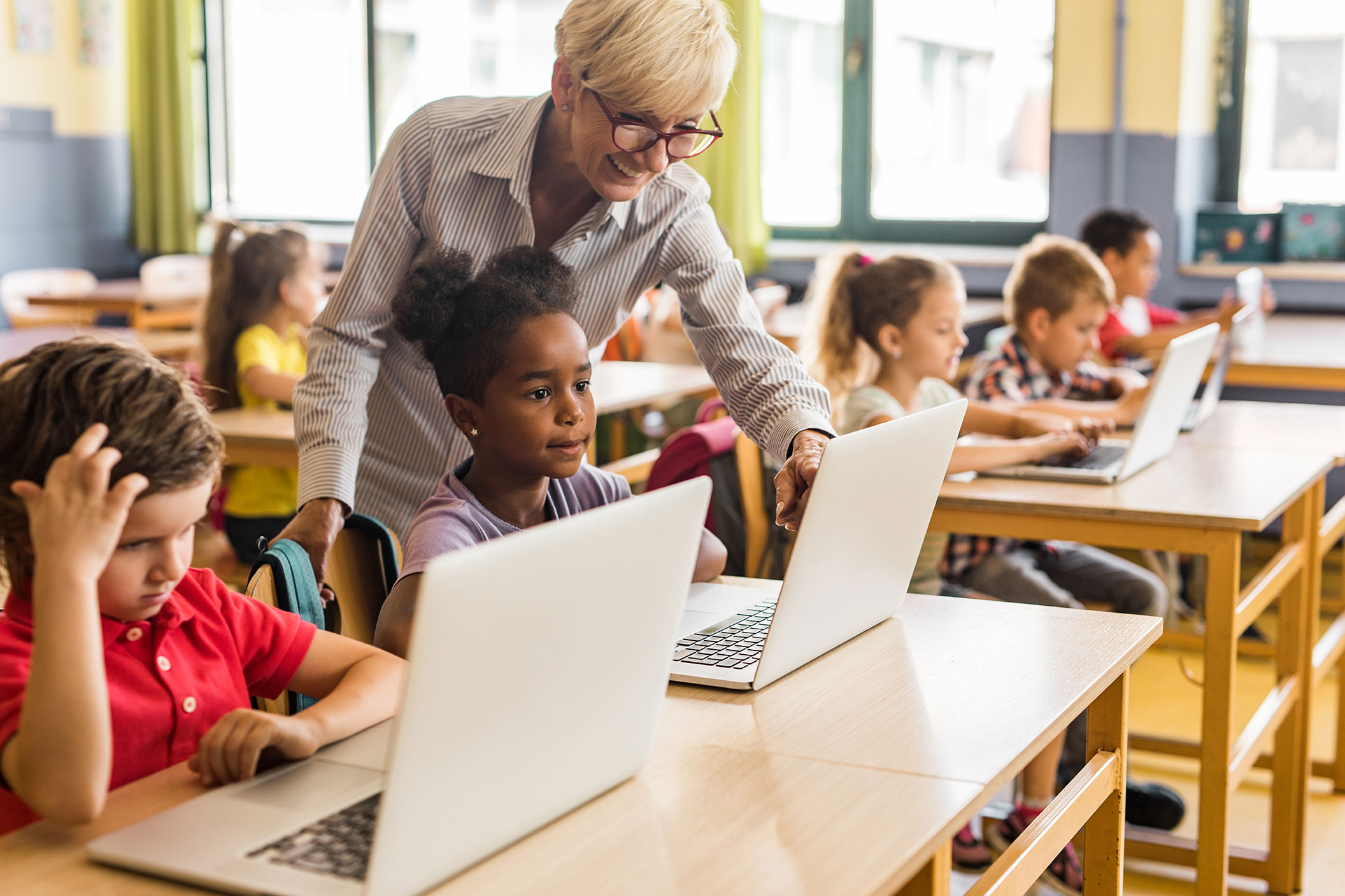 Teacher with students in classroom setting with computers